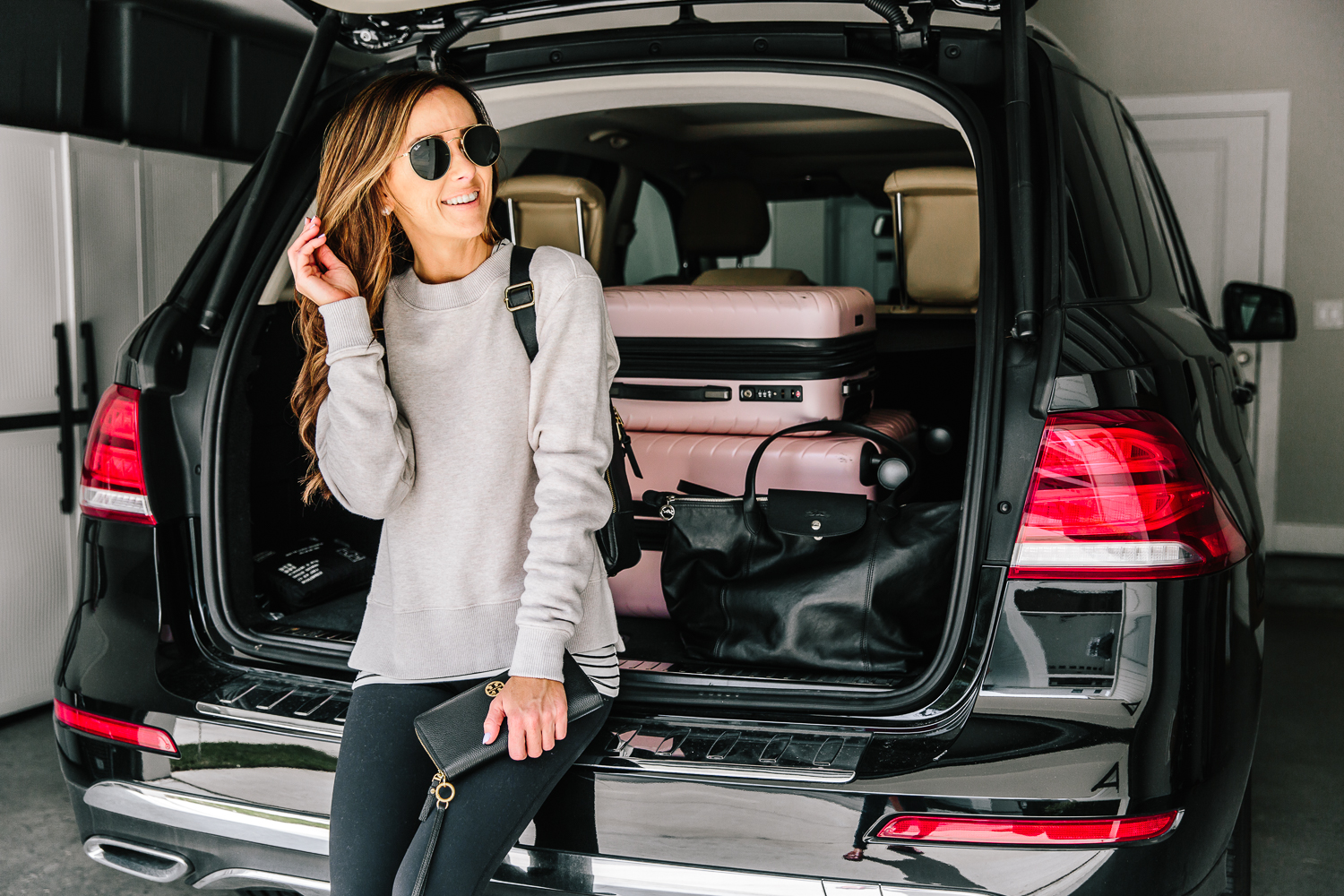pink chevron spinner luggage set loaded into back of car